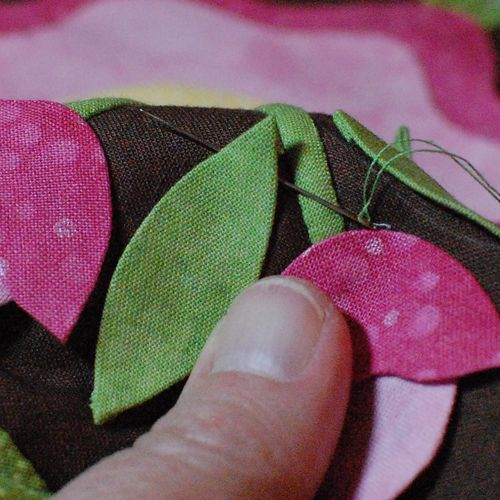 34.Start stitching by slipping needle into fold on applique shape (on the front of the block)